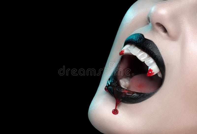 Vampire teeth with dripping blood, Woman`s black bloody lips close-up. Vampire girl fangs. Fashion Halloween art design royalty free stock images