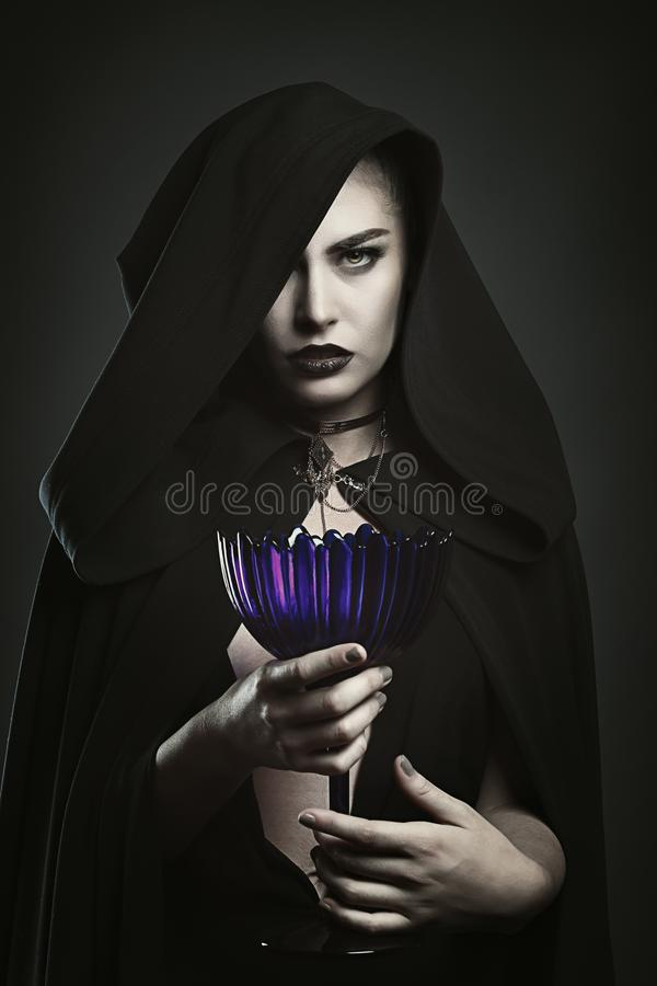 Vampiro bonito que guarda um copo imagens de stock