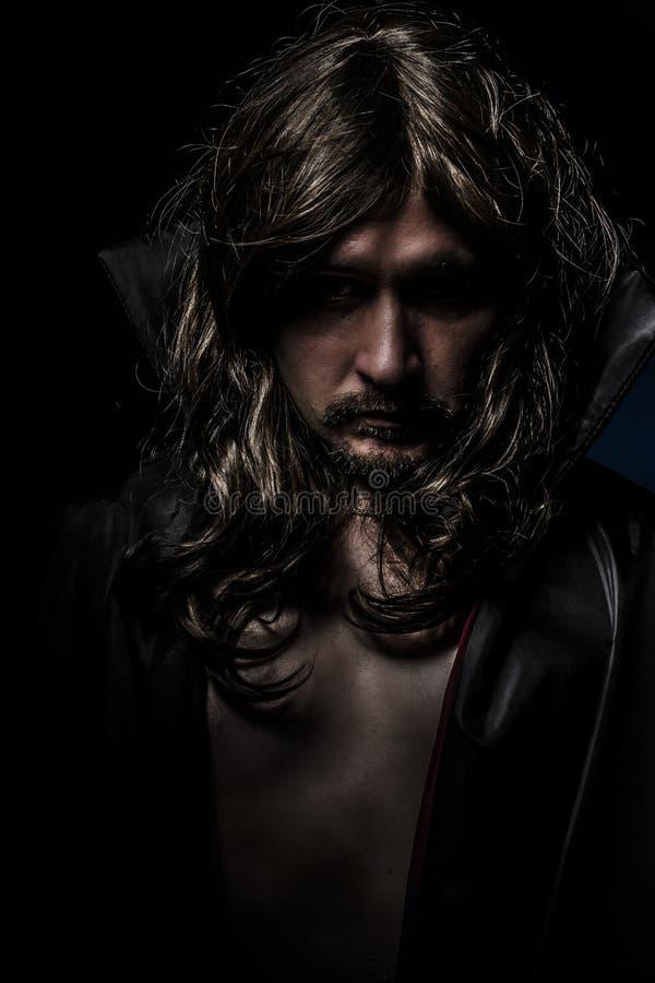 Vampiro con la capa negra y el pelo largo, tristes fotografía de archivo