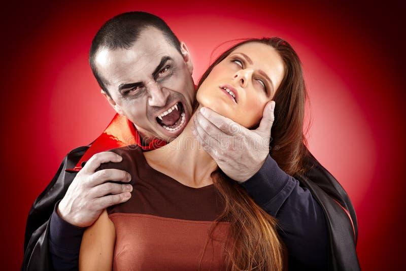 Vampiro que prepara-se para morder sua vítima fotografia de stock