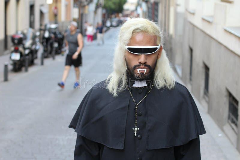 Vampiro vestido como un sacerdote que camina al aire libre imagen de archivo libre de regalías
