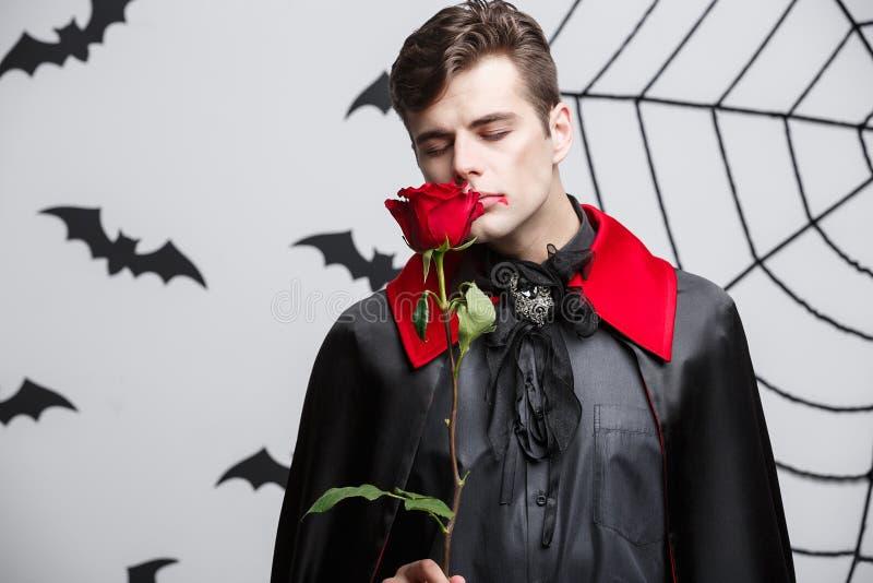 Vampirs-Halloween-Konzept - Porträt des hübschen kaukasischen Vampirs, der rotes schönes hält, stieg lizenzfreies stockfoto