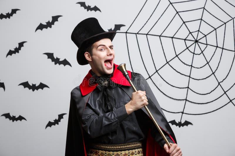 Vampirs-Halloween-Konzept - Porträt des hübschen kaukasischen Vampirs in schwarzem und rotem Halloween-Kostüm singend mit Persona lizenzfreie stockfotografie