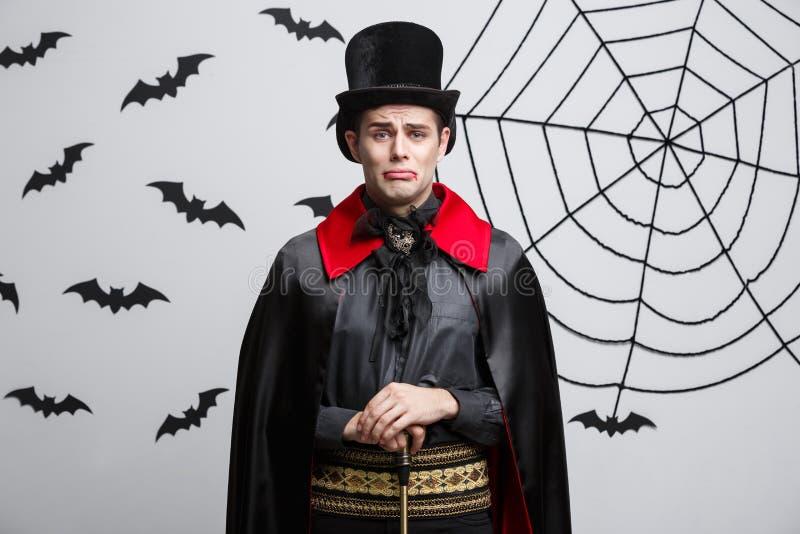Vampyrallhelgonaaftonbegrepp - stående av den stiliga caucasianen i den vampyrhalloween dräkten med ledset ansiktsuttryck royaltyfri bild