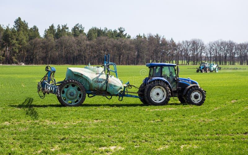 11 van April, 2018 - Vinnitsa, de Oekraïne Tractor het bespuiten insectici stock afbeelding