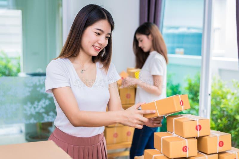 Van bedrijfs twee jonge Aziatische meisjesfreelancers eigenaar die thuis bureau werken en pakketpostdoos sorteren aan de levering stock foto