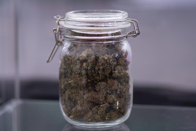 Van bloemen van cannabis en schalen en gezamenlijke hoogste mening ter beschikking een molen om marihuanaonkruid tegen een achter stock afbeelding