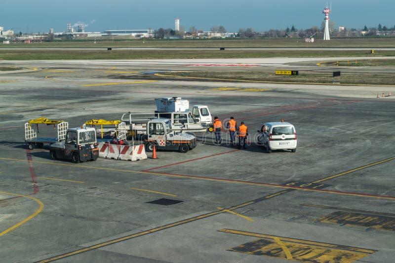"""VAN BOLOGNA, ITALIË Â€ """"18 FEBRUARI: Luchthavenarbeiders die op een vliegtuig t wachten royalty-vrije stock foto"""