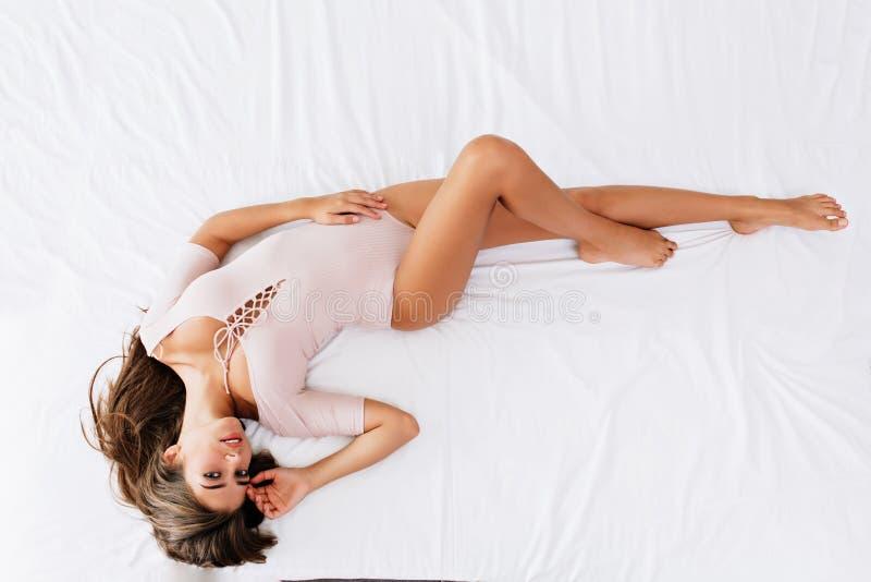 Van boven jong donkerbruin meisje dat met lang haar op wit bed legt Zij draagt sensuele kleren, wat betreft gezicht, kijkend aan royalty-vrije stock foto's