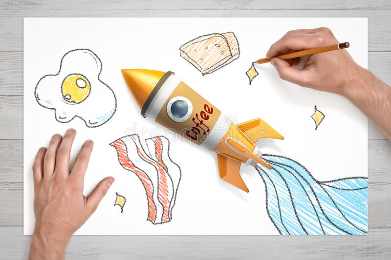 Van boven naar boven kijken van handen die brood tekenen, en eieren en bacon op wit vel papier, met een speelgoedraket gemaakt va stock afbeeldingen