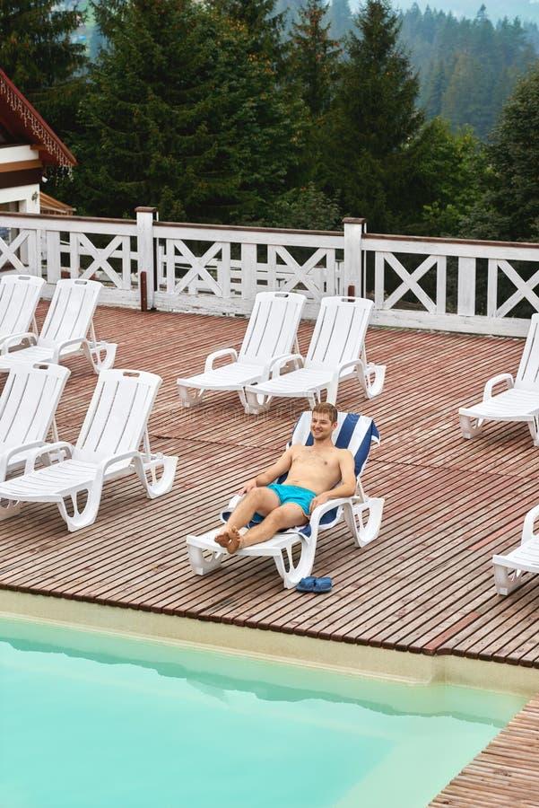 Van bovengenoemde mening die van sportieve jongen, op witte ligstoel ontspannen stock foto