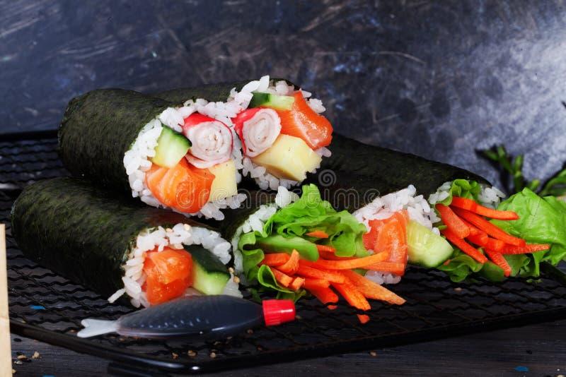 Van broodjessushi zwarte verschillende smaken als achtergrond, krab, wortelen, sla, tofu, zalm, stilleven, houten huis, modieus, stock afbeelding
