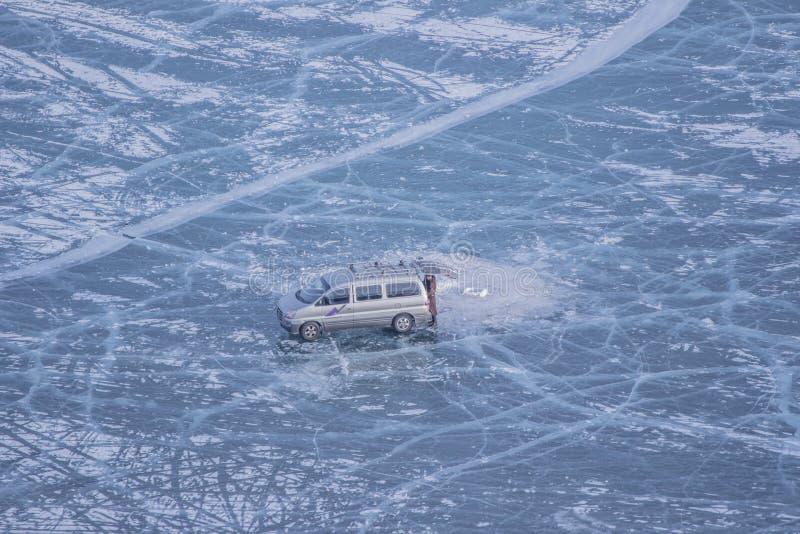 Van carro e homem solitário no lago congelado Khovsgol e textura da quebra em Mongólia fotografia de stock