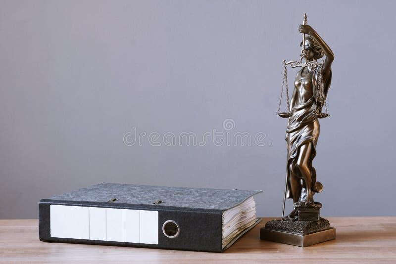 Van damerechtvaardigheid of justitia standbeeld en dossieromslag op bureau royalty-vrije stock foto's