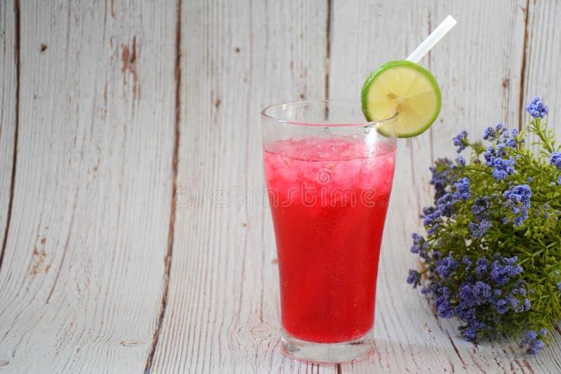 Van de 'rode Sodacitroen 'de drank, op een grijze houten achtergrond, met citroenstukken op het glas stock afbeeldingen