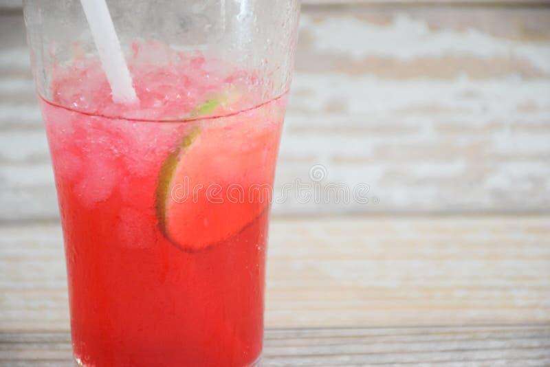 Van de 'rode Sodacitroen 'de drank, op een grijze houten achtergrond, met citroenstukken op het glas stock fotografie