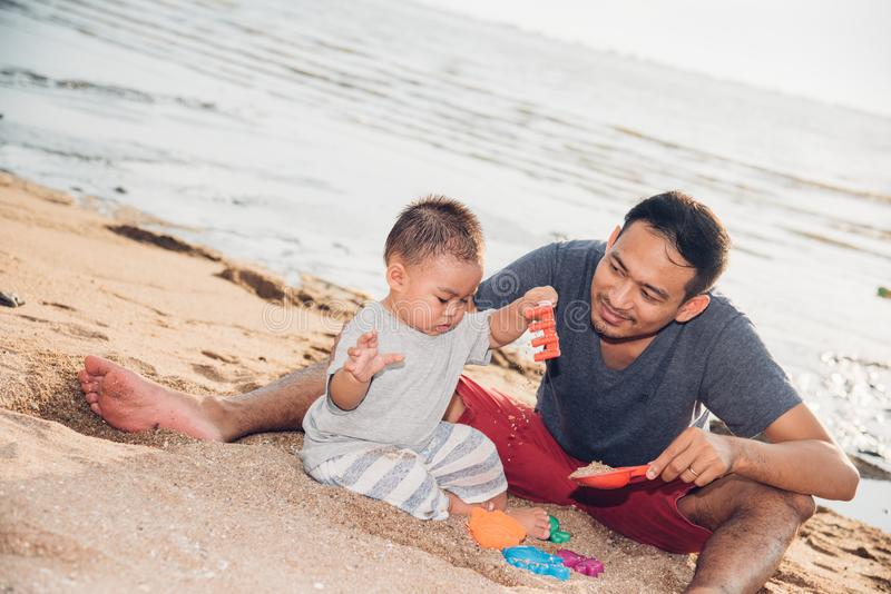 Van de babyjongen en vader papa speelpret op zandstrand stock afbeeldingen