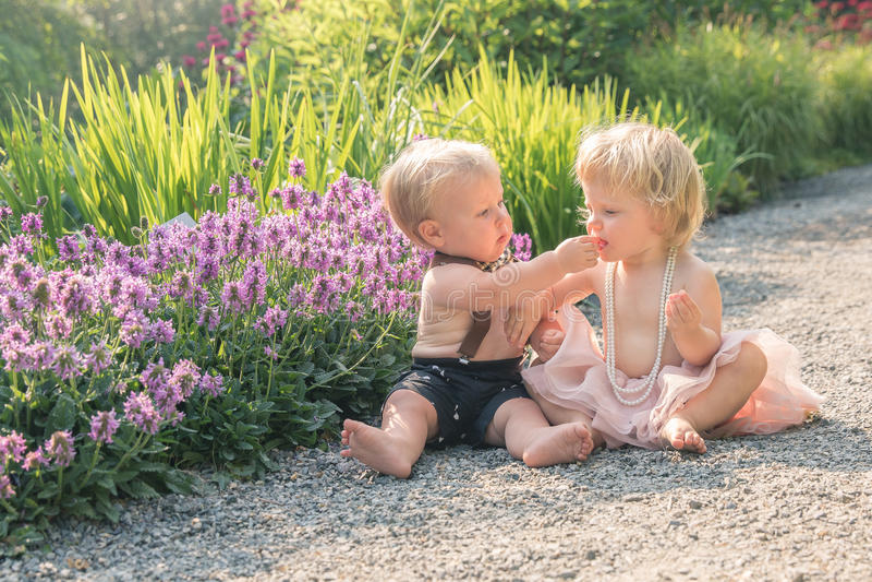 Van de babymeisje en jongen zitting in een mooie tuin en het richten aan purpere bloem royalty-vrije stock afbeelding