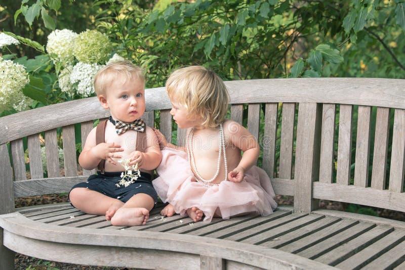 Van de babymeisje en jongen zitting op houten bank royalty-vrije stock foto's