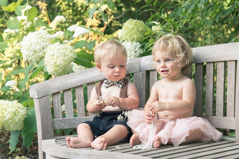 Van de babymeisje en jongen zitting op houten bank en het kijken op parel royalty-vrije stock foto's