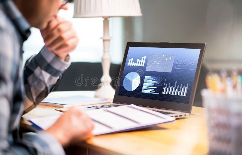Van de bedrijfs mensenlezing rapportdocument Laptop met financiële grafieken stock foto's