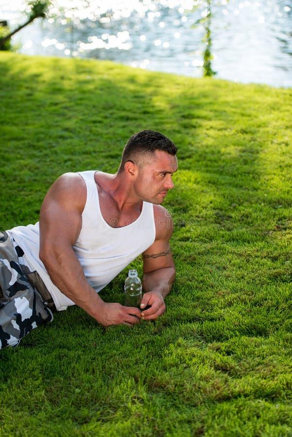 Van de bodybuilder het Rusten en Holding Waterfles stock foto