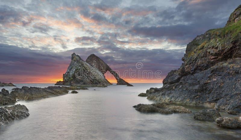 Van de boog-fidle-boog het landschap Rotszonsopgang op de kust van Schotland op bewolkte ochtend stock afbeelding