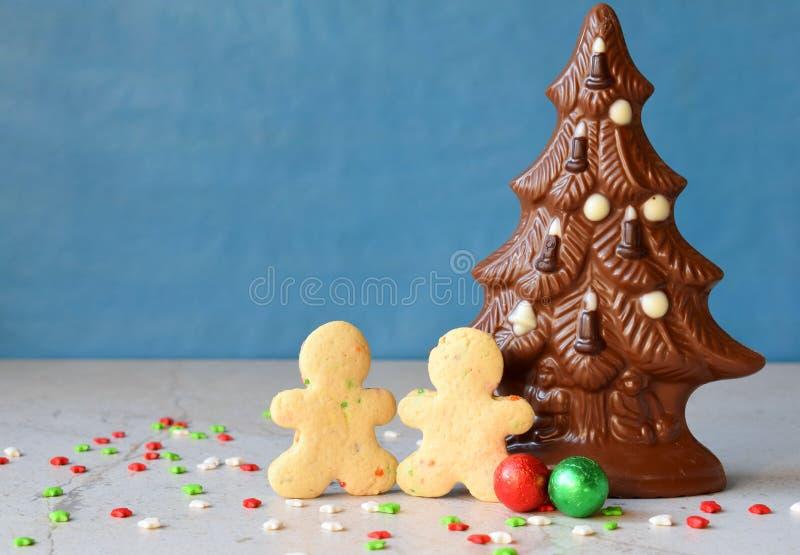 Van de chocoladekerstboom en peperkoek mensen op blauwe achtergrond Gelukkig nieuw jaar en Vrolijk Kerstmisconcept De ruimte van  stock afbeeldingen