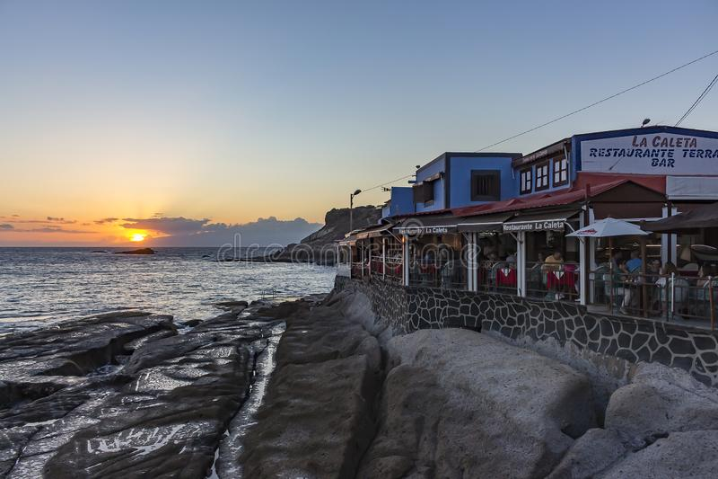 Van de comfortabele vissenrestaurants langs de kust van La Caleta, Costa Adeje op Tenerife, Spanje, kunt u de zon zien erachter v royalty-vrije stock afbeelding