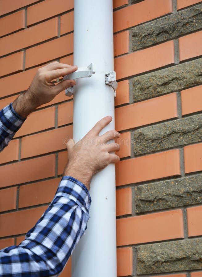 Van de contractant het installeren en reparatie van het de dakgootsysteem van pvc de pijpleidingshouder Plastic Guttering, & Drai stock foto's