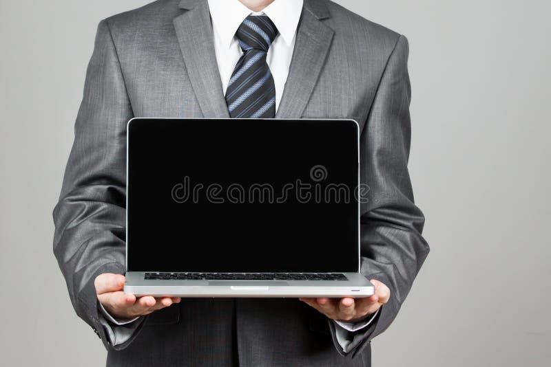 Van de de handgreep van de zakenman bevindende houding het notitieboekjelaptop stock afbeelding