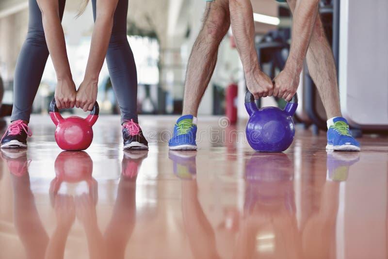 Van de de oefeningsman en vrouw van de Kettlebellsschommeling training bij gymnastiek stock fotografie