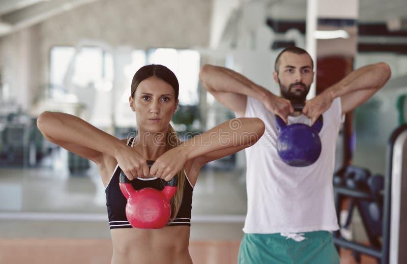 Van de de oefeningsman en vrouw van de Kettlebellsschommeling training bij gymnastiek royalty-vrije stock foto's