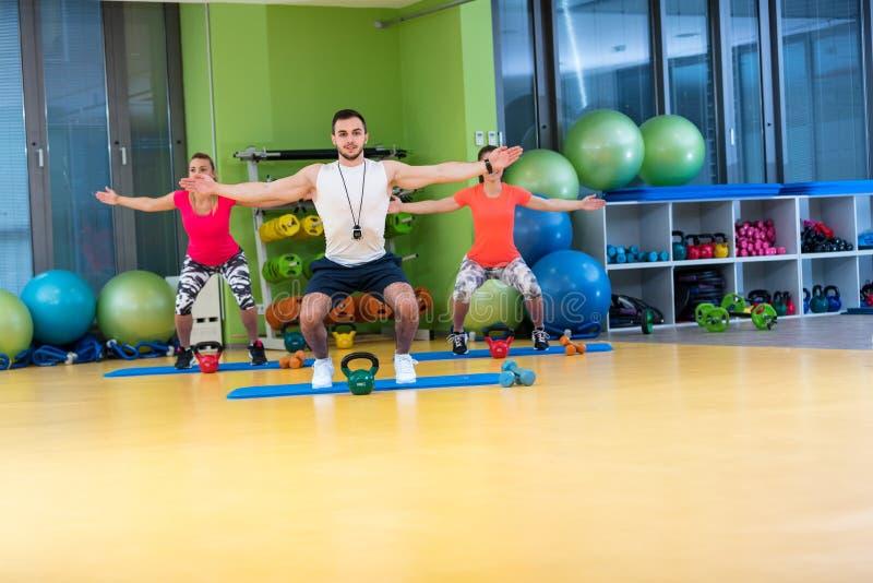 Van de de oefeningsman en vrouw van de Kettlebellsschommeling training bij gymnastiek stock afbeeldingen