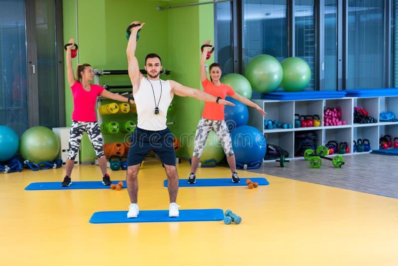 Van de de oefeningsman en vrouw van de Kettlebellsschommeling training bij gymnastiek stock foto