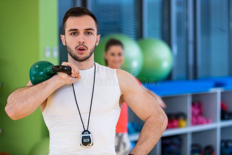 Van de de oefeningsman en vrouw van de Kettlebellsschommeling training bij gymnastiek stock afbeelding