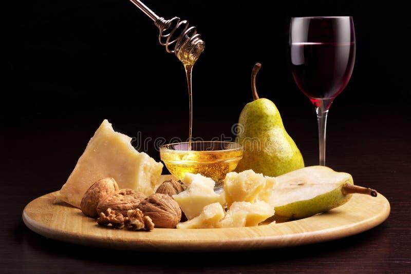 Van de de perenhoning van de parmezaanse kaaskaas de okkernoten en het wijnglas stock afbeelding