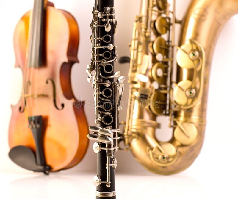Van de de teneursaxofoon van de saxofoon de viool en de klarinet in wit stock foto