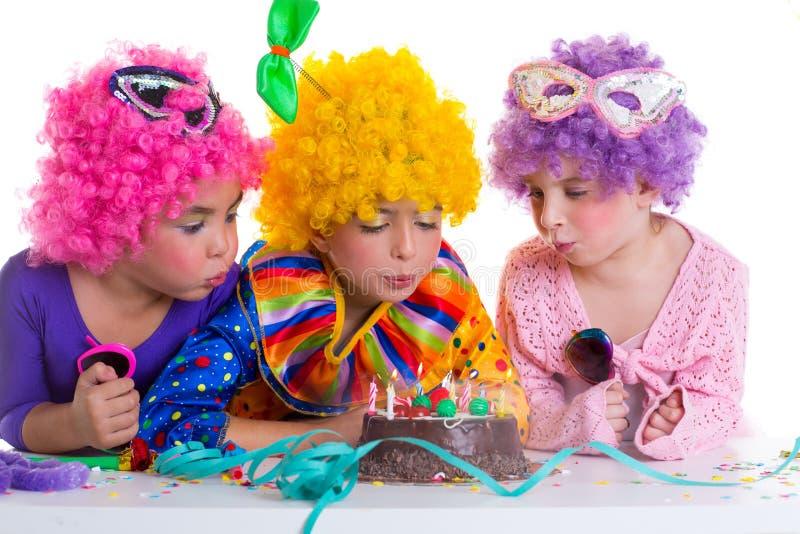 Van de de verjaardagspartij van kinderen de clownpruiken die cakekaarsen blazen royalty-vrije stock fotografie