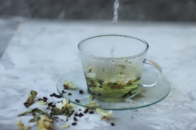 Van de Detoxvoedsel en drank healfhy levensstijlconcept Glaskop van groene thee met jasmijn op een grijze achtergrond sluit royalty-vrije stock fotografie