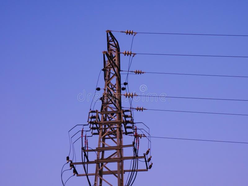 Van de elektriciteitspyloon en macht kabels bij schemer tegen blauwe hemel stock foto