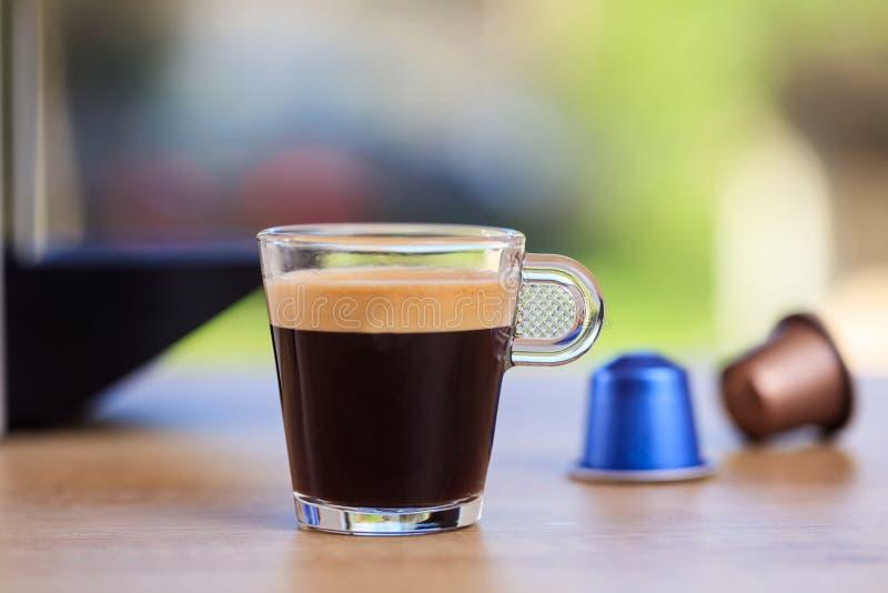 Van de espressokop en koffie capsules op onduidelijk beeldachtergrond, Close-upmening met details royalty-vrije stock afbeeldingen