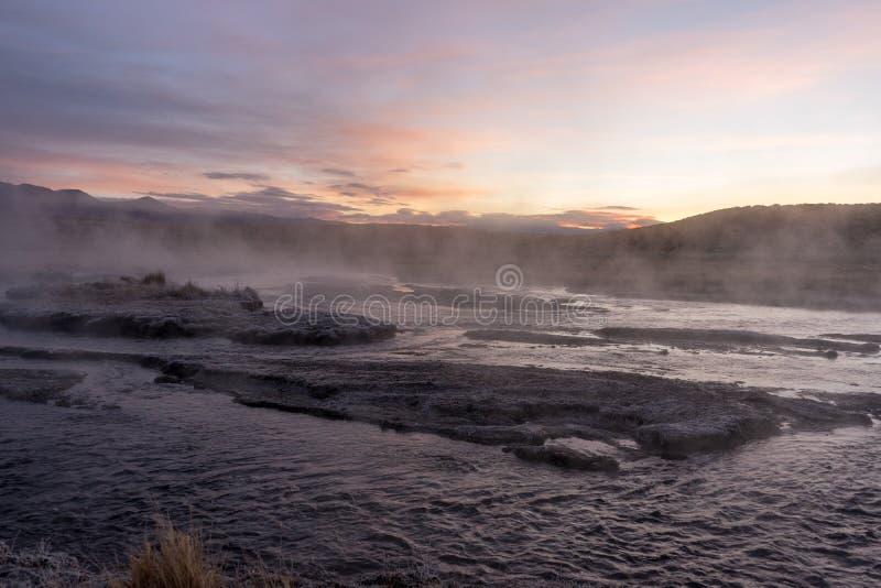 Van de geslagen weg die op een zonsopgang letten over een stomende rivier van geothermisch water royalty-vrije stock afbeelding