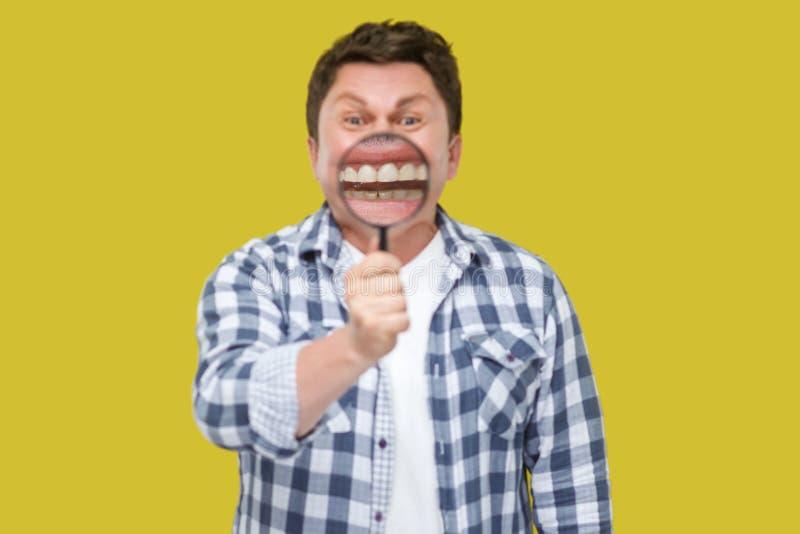 Van de glimlachgezoem of tand zorgconcept Portret die van de midden oude mens in toevallig geruit overhemd die, vergrootglas op v stock afbeeldingen