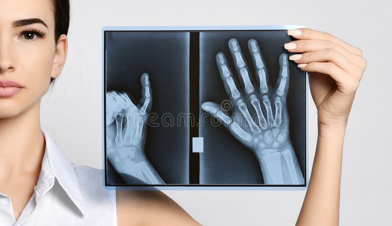 Van de greephanden van de artsenvrouw de Röntgenstraalonderzoek op grijs stock afbeelding