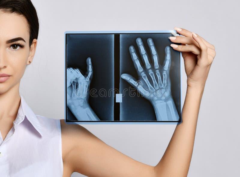 Van de greephanden van de artsenvrouw de Röntgenstraalonderzoek op grijs royalty-vrije stock afbeelding