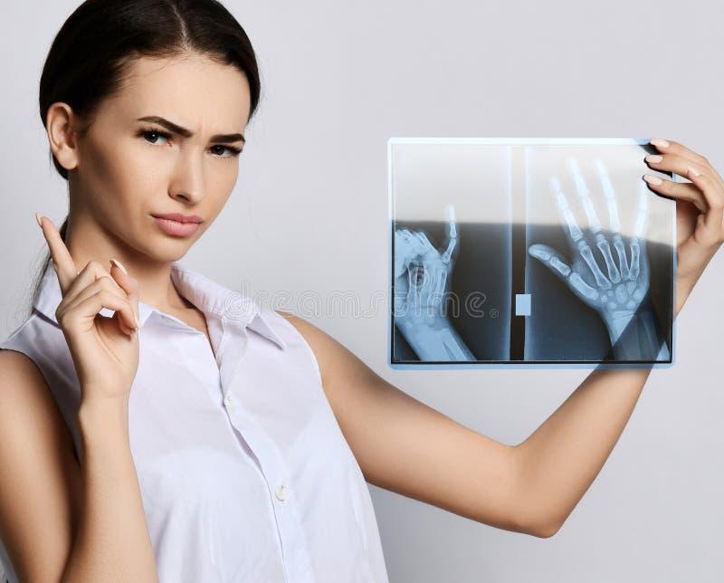Van de greephanden van de artsenvrouw de R?ntgenstraalonderzoek op grijs royalty-vrije stock fotografie