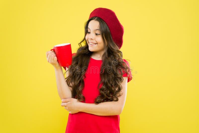 Van de de greepmok van het meisjesjonge geitje de gele achtergrond De mok van de kindgreep De drinkende cacao van het theesap Het stock foto's