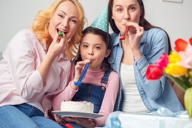 Van de grootmoedermoeder en dochter samen thuis verjaardagszitting die de blazende gelukkige hoornen koesteren van de holdingscak stock foto's