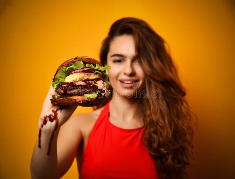 Van de de hamburgersandwich van de vrouwengreep de grote in hand hongerige mond die klaar te eten worden royalty-vrije stock fotografie